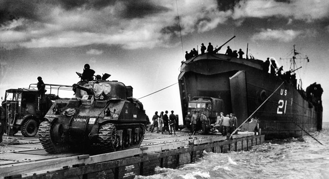 "The U.S. Coast Guard manned USS LST-21 unloads British Army tanks and trucks onto a ""Rhino"" barge during the early hours of the invasion on Gold Beach. 6th June 1944. Normandy, France. Source: Source: UllsteinBild / Vostock_photo"