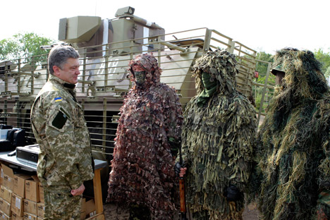 The Kommersant daily writes that the Ukrainian Army, on the orders of President Petro Poroshenko (left), has resumed its offensive in the east. Source: AP