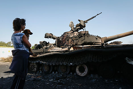 A woman looks at a burned Ukrainian tank in the village of Kominternovo, on the outskirts of the southern coastal town of Mariupol. Vladimir Putin and Petro Poroshenko agreed on Saturday that a ceasefire in eastern Ukraine was generally holding.  Source: Reuters