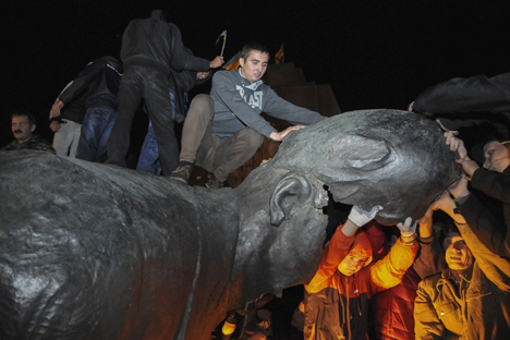 People react after a statue of Soviet state founder Vladimir Lenin was toppled by protesters during a rally organized by pro-Ukraine supporters in the centre of the eastern Ukrainian town of Kharkiv September 28, 2014. Source: Reuters