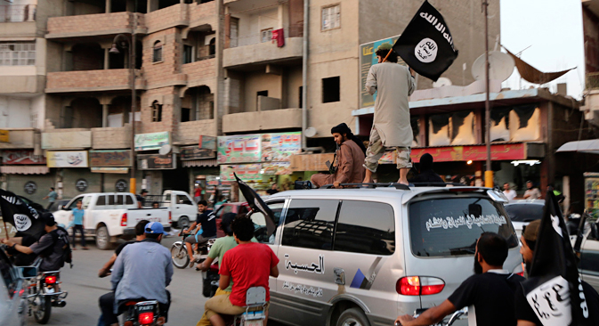 Members loyal to the Islamic State in Iraq and the Levant (ISIL) wave ISIL flags as they drive around Raqqa June 29, 2014. Source: Reuters