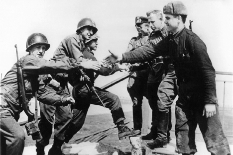 American (left) and Russian soldiers shake hands on April 24, 1945 at the destroyed bridge over river Elbe as both troops meet at Torgau, Germany.