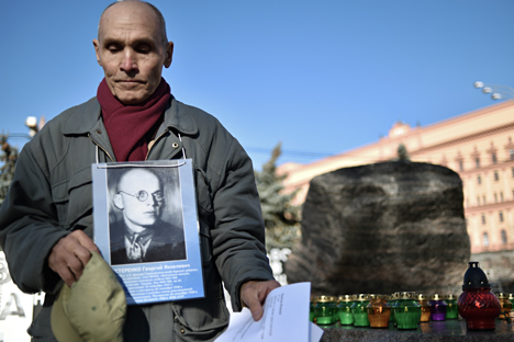 A man holds his father's portrait near the memorial to the victims of Soviet-era political repression, the Solovky Stone monument, on Lubyanka Square in Moscow, on October 29, 2014.