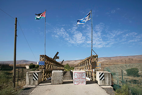 National Jordanian and Israeli flags are seen on the Naharayim bridge on the border between Israel and Jordan north-eastern Israel October 22, 2014.