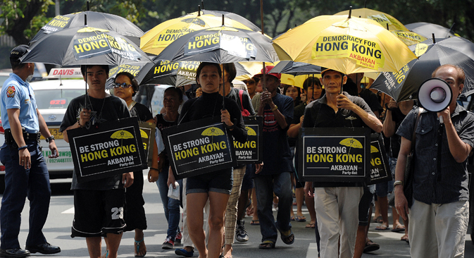 Filipino activists carrying umbrellas painted with slogans, march towards the Chinese consular office to show their support for Hong Kong pro-democracy protesters during a rally in the financial district of Manila on October 2, 2014. Source: AFP / East NEws