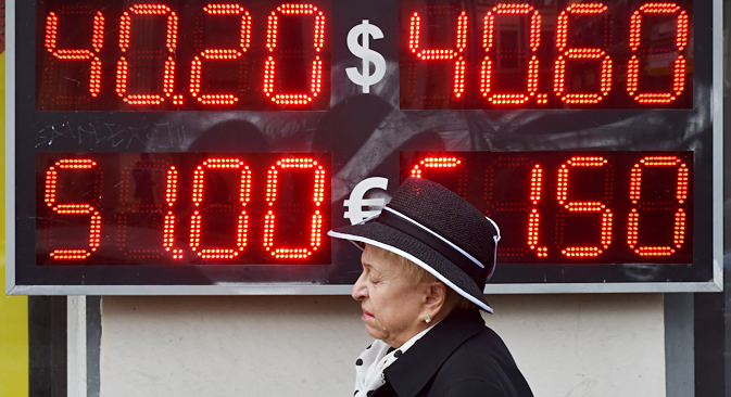 A woman walks under a board listing foreign currency rates against the Russian ruble, outside an exchange office in central Moscow, on October 13, 2014. Source: AFP/East News