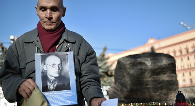 A man holds his father's portrait near the memorial to the victims of Soviet-era political repression, the Solovky Stone monument, on Lubyanka Square in Moscow, on October 29, 2014. Source: AFP / East News