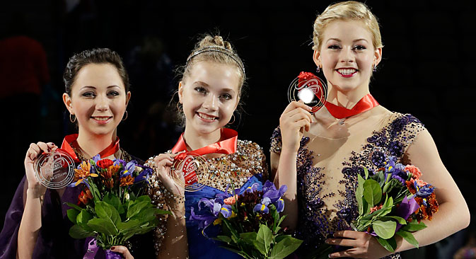 Elena Radionova (center), Elizaveta Tuktamysheva (left), and Gracie Gold pose for photographers with their medals for the ladies skating program at the Skate America figure skating event. Source: AP
