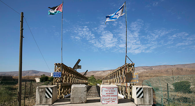 National Jordanian and Israeli flags are seen on the Naharayim bridge on the border between Israel and Jordan north-eastern Israel October 22, 2014. Source: Reuters