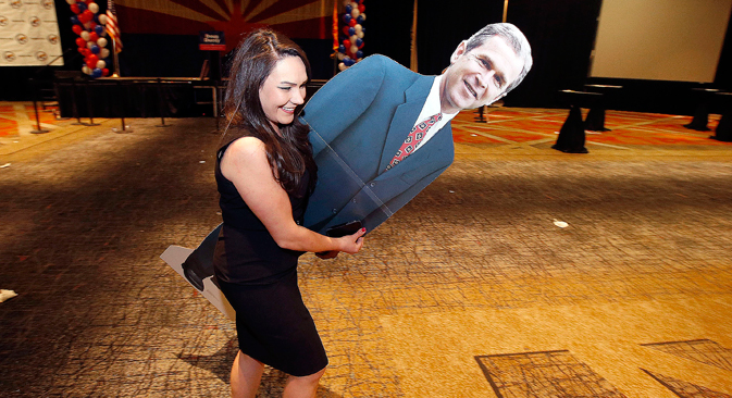 Katie Granger leaves the Republican election night festivities party with a photo cutout of former President George W. Bush, Tuesday, Nov. 4, 2014, in Phoenix. Source: AP
