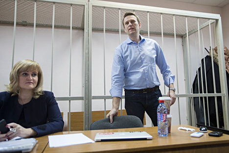 Russian opposition activist and anti-corruption crusader Alexei Navalny, right, waits for a start of a trial in a courtroom in Moscow, Russia, Friday, Dec. 19, 2014. Navalny, who has been under house arrest since February, is being charged in a second trial that may put him behind bars for good. Source: AP