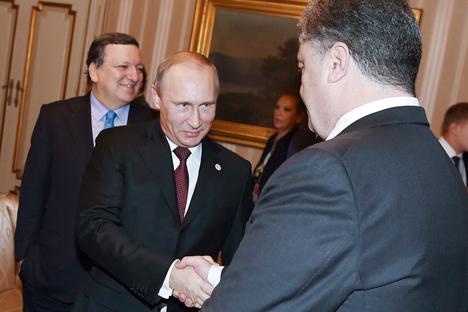 Pútin (à esq.) cumprimenta o presidente ucraniano Petrô Porochenko em reunião realizada no ano passado Foto: Reuters