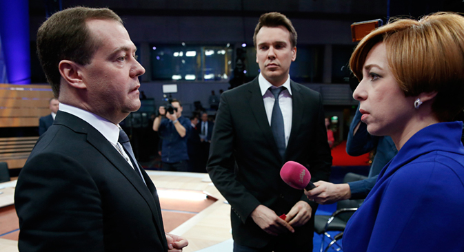Russia's Prime Minister, Dmitry Medvedev, left, speaks during a live nation-wide TV show at Moscow's Ostankino TV center, Russia, Wednesday, Dec. 10, 2014. Mikhail Zygar of Dozhd, center, and Marianna Maksimovskaya of REN TV listen. Source: AP