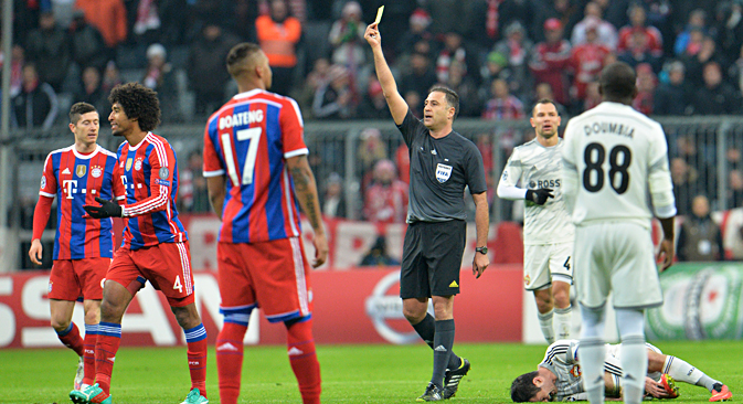 Bayern's Dante from Brazil, second left, is booked by referee Olegario Benquerenca after he fouled CSKA's Alan Dzagoev, right, during the Champions League group E soccer match between FC Bayern Munich and CSKA Moscow in Munich, Germany, Wednesday, Dec. 10, 2014. Source: AP