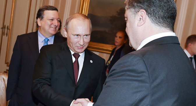 Russia's President Vladimir Putin (L) shakes hands with Ukraine's President Petro Poroshenko as he arrives for a meeting on October 17, 2014. Source: Reuters