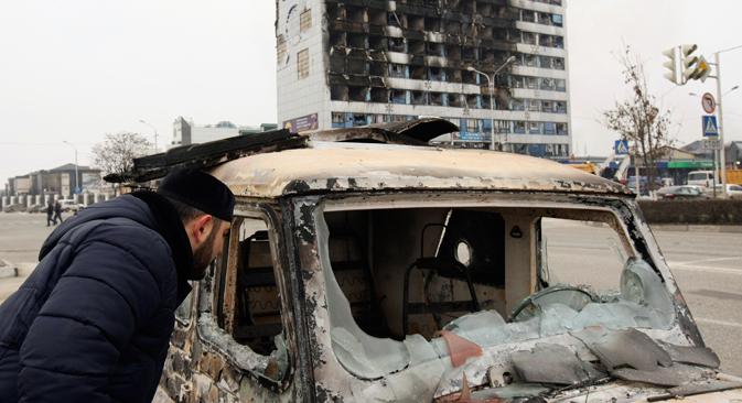 Čovjek zaviruje u spaljeni auto kraj Novinarskog doma, zgrade lokalne novinske agencije u čečenskom glavnom gradu Groznom, 3. prosinca, 2014. Najmanje šest napadača i tri policajca je ubijeno u oružanim bitkama u kojima je izvršen upad u čečenski glavni grad Grozni u utorak, izjavio je lider ove turbulentne južne ruske regije. Izvor: Reuters