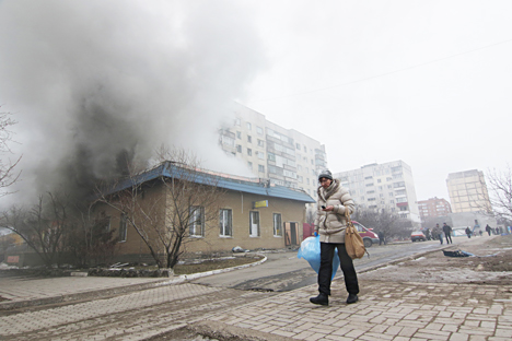 A woman resident passes by a burning house in Mariupol, Ukraine, Saturday, Jan. 24, 2015. Source: AP