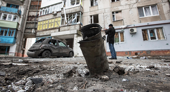 A piece of an exploded Grad missile is photographed as a man takes a photo of a burned car in the background, outside an apartment building in Vostochniy, district of Mariupol. Source: AP