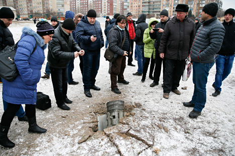 People look at the remains of a rocket shell on a street in the town of Kramatorsk, eastern Ukraine February 10, 2015. Three people were killed and 15 wounded in the rocket strike on the town of Kramatorsk on Tuesday, the government-controlled regional administration said in a statement. Source: Reuters