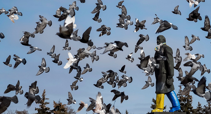 Pigeons fly around a monument of the Soviet state founder Vladimir Lenin painted in the colors of the Ukrainian national flag is seen in Kramatorsk, eastern Ukraine February 11, 2015. Source: Reuters