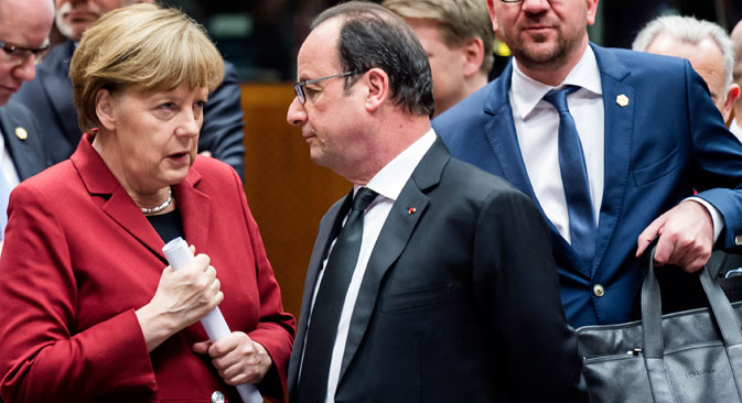 German Chancellor Angela Merkel, left, speaks with French President Francois Hollande, center, during a round table meeting at an EU summit in Brussels on Thursday, March 19, 2015. Source: AP