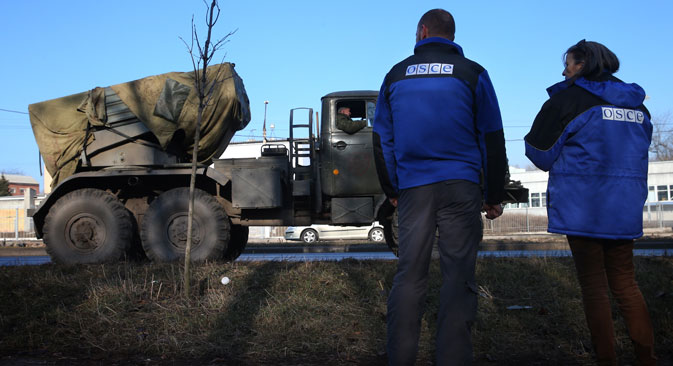 OSCE officials watch Grad multiple-launch rocket systems being withdrawn by Donetsk People's Republic troops from the outskirts of Donetsk. Source: Valery Sharifulin / TASS