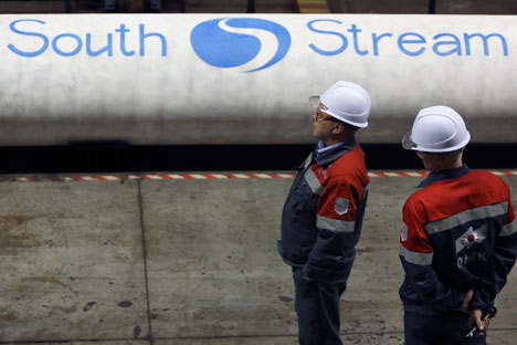 Employees stand near pipes made for the South Stream pipeline.
