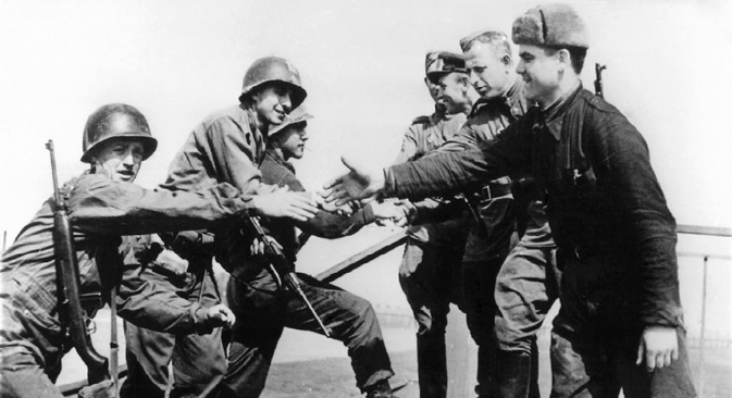American (left) and Russian soldiers shake hands on April 24, 1945 at the destroyed bridge over river Elbe as both troops meet at Torgau, Germany. Source: DPA/AFP/East-News