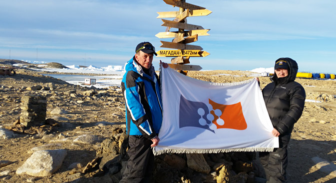 Valery Vladimirov and Yury Fateyev hold the flag of the Siberian Federal University at the Novolazarevskaya station in Antarctica. Source: Valery Vladimirov / Siberian Federal University