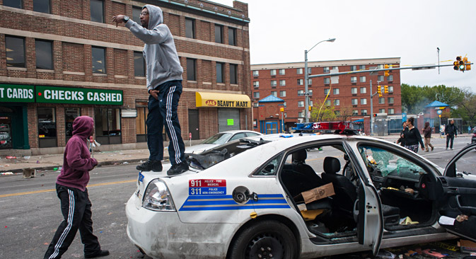 A protestor stands on a destroyed Baltimore City Police car on North Avenue during a protest for the death of Freddie Gray in Baltimore, Maryland, USA, 27 April 2015. Source: EPA