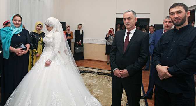 The bride, Kheda Goylabiyeva, and groom, police officer Nazhud Guchigov, second right, stand in a wedding registry office in Chechnya's capital Grozny, on May 16. On the right is head of the Chechen leader's administration Magomed Daudov. Source: AP