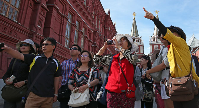 Tourists near the State Historical Museum of Russia in front of the Resurrection Gate, Moscow. Source:  ITAR-TASS/ Artyom Geodakyan