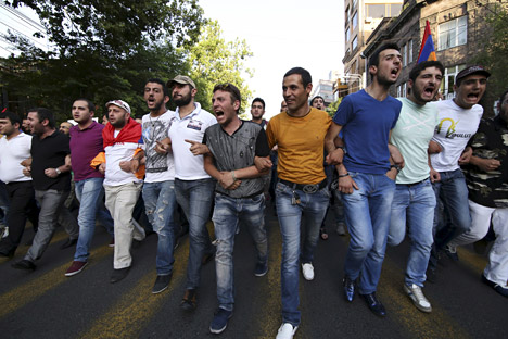 Protesters march during a rally against a recent decision to raise public electricity prices in Yerevan, Armenia. Source: Reuters