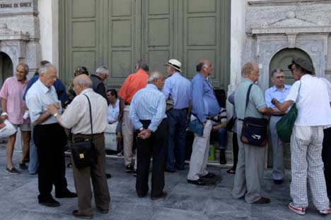 People, mostly pensioners who do not own an ATM card, wait in line outside a National Bank of Greece branch, in Athens, Greece, 29 June 2015. Source: EPA / Orestis Panagiotou