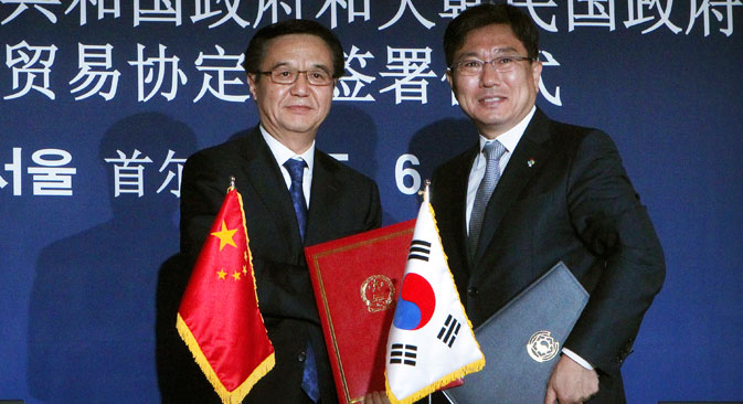 Chinese Commerce Minister Gao Hucheong, left, poses with his South Korean counterpart Yoon Sang-jick after signing documents for FTA or Free Trade Agreement during a signing ceremony in Seoul, South Korea. Source: AP
