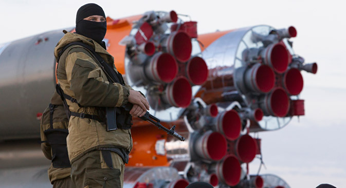 An armed security guard stands in front of the Soyuz TMA-14M spacecraft, as it is transported to its launch pad at Baikonur cosmodrome September 23, 2014. Source: Reuters