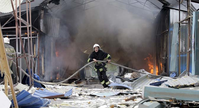 A firefighter works to extinguish a fire at a local market, which was recently damaged by shelling, in Donetsk, Ukraine, June 3, 2015. Source: AP