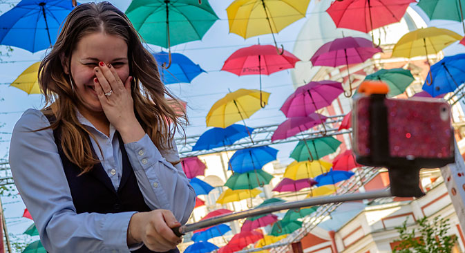 A girl takes a selfie in front of five hundred colourful umbrellas hanging above Solyanoi Side Street near the Stieglitz Saint Petersburg State Art and Industry Academy as part of a public art installation. Source: Ruslan Shamukov / TASS