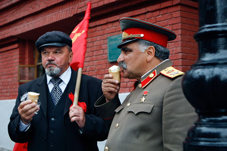 Vladimir Lenin(left) and Joseph Stalin look-a-likes eat ice cream as they share a minute of rest in downtown Moscow.