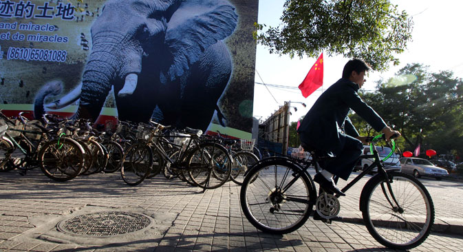 A man cycles past a billboard which promotes the China-Africa summit meeting on a street in Beijing. Source: AP/ Greg Baker