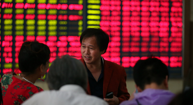 An investor talks with the others at a stock exchange in Nantong , Jiangsu province, China on 9th July 2015. Source: Vostock photo