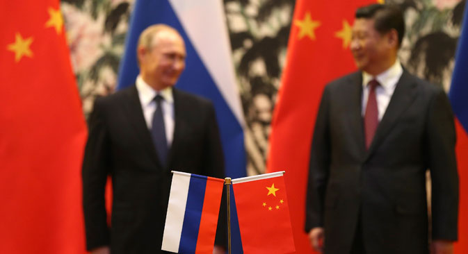 Russian and Chinese national flags are seen on the table with Russian President Vladimir Putin (L) and his Chinese counterpart Xi Jinping (R), Beijing, November 9, 2014.