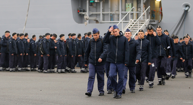 Russian sailors walk in front of the Mistral-class helicopter carrier Vladivostok at the STX Les Chantiers de l'Atlantique shipyard site in Saint-Nazaire, western France, November 25, 2014. Source: Reuters