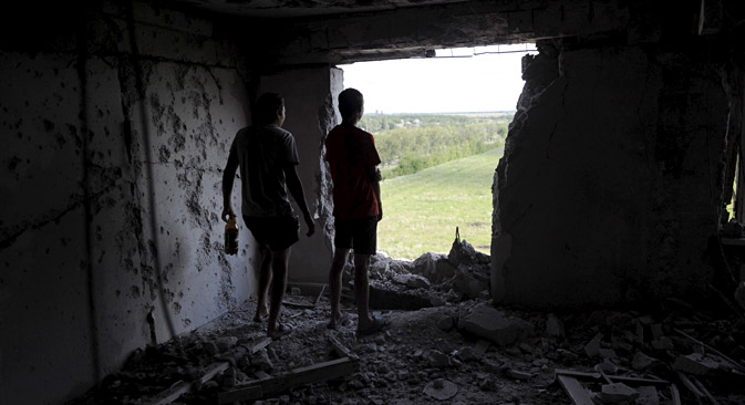 Local residents look through a hole in a damaged multi-story building, which according to locals was caused by recent shelling, in Avdeyevka, Donetsk Region, July 18, 2015. Source: Reuters