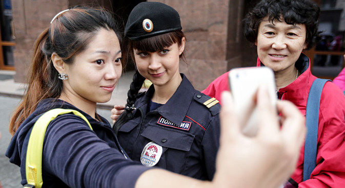 Tourists making selfy with an employee of the tourist police in Moscow. Source: TASS