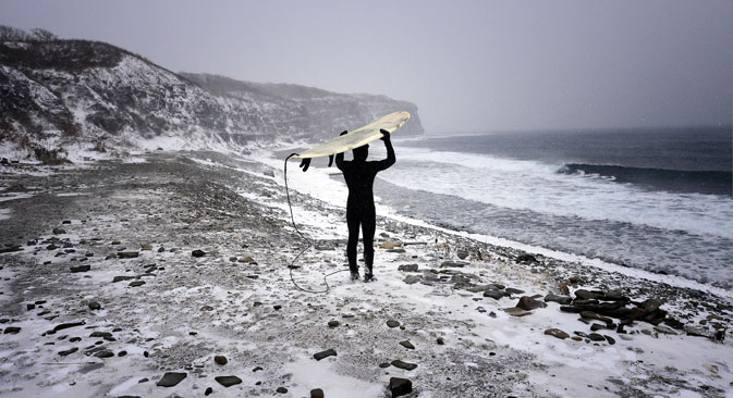 A man with his surfboard walking along the Ussuri Bay coast on Russky Island, Dec. 21, 2014. Source: Yuri Smityuk/TASS