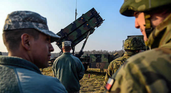 The U.S. (left) and Polish soldiers stand next to a launcher vehicle of a US 'Patriot' air defence guided missile system battery positioned on a military training ground near Sochaczew, Poland, 21 March 2015. Source: EPA / Vostock-photo