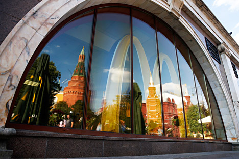 The walls and towers of the Kremlin are reflected in a window of a closed McDonald's restaurant. Source: Reuters
