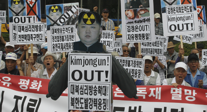 South Korean protesters with defaced portraits of North Korean leader Kim Jong Un and North Korean flags shout slogans during an anti-North Korean rally in Seoul, South Korea, Friday, Aug. 21, 2015.