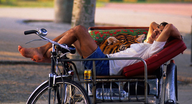 A man sleeping in a rickshaw in Esplanade Park, Singapore. Source: Photoshot/Vostock Photo
